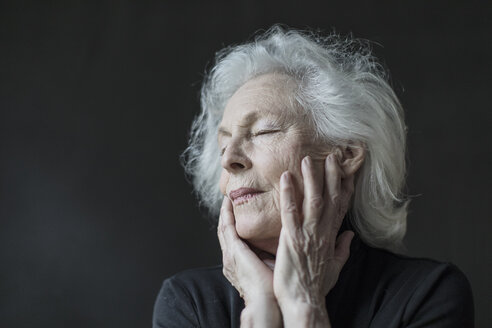 Close-up of relaxed senior woman with hands on face against black background - TGBF00337