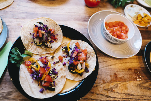 High angle view of delicious Mexican tacos in plate on wooden table at home - TGBF00415