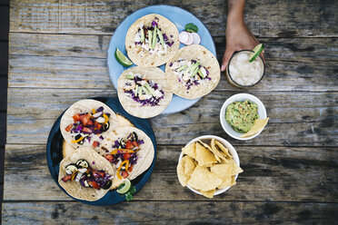 Female's hand holding glass of drink by Mexican tacos and nacho chips on wooden table - TGBF00418