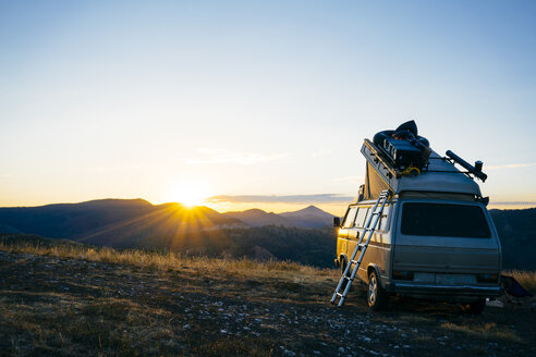 Camper parked on grassy field against clear sky at Grand Teton National Park during sunset - TGBF00424