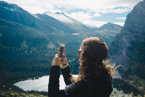Side view of woman photographing through mobile phone while standing by mountains at Glacier National Park - TGBF00430