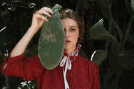 Portrait of a woman who covers her face with a cactus leaf - INGF05339