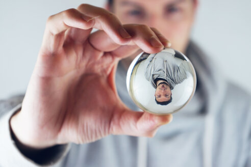 Close-up portrait of man holding reflective ball - INGF05372