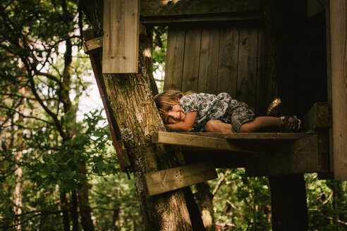 Young boy relaxing in tree house in forest looking into camera - INGF05387