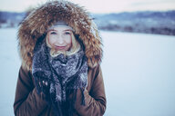 Portrait of smiling young woman in the snow during winter - INGF05393