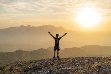 Spain, Barcelona, Natural Park of Sant Llorenc, man hiking and cheering at sunset - AFVF01890