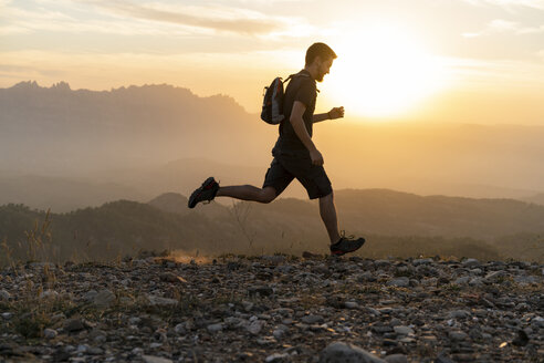Spain, Barcelona, Natural Park of Sant Llorenc, man running in the mountains at sunset - AFVF01893