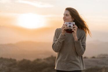 Spain, Barcelona, Natural Park of Sant Llorenc, woman with vintage camera at sunset - AFVF01899