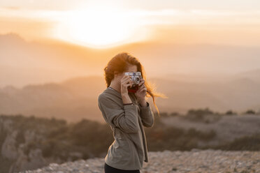 Spain, Barcelona, Natural Park of Sant Llorenc, woman taking a picture with vintage camera at sunset - AFVF01902