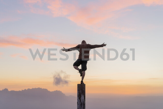 Spain, Barcelona, Natural Park of Sant Llorenc, man standing on pole at sunset - AFVF01908 - VITTA GALLERY/Westend61