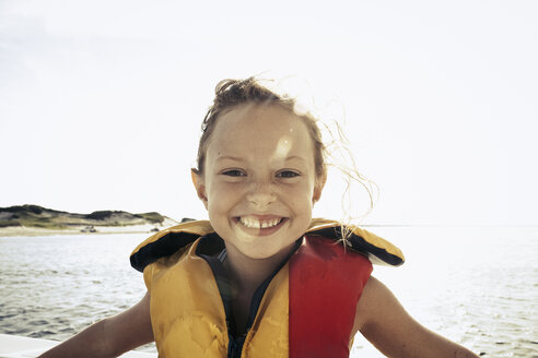 Smiling girl wearing life-jacket on boat - TGBF00532