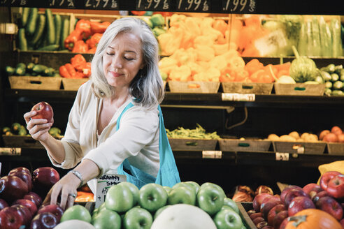 Mature woman smiling while buying apples at supermarket - TGBF00538