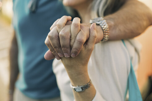 Close-up of mature couple holding hands while standing outdoors - TGBF00553