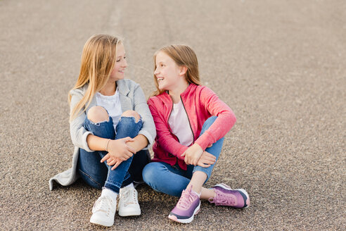 Two smiling girls sitting side by side on the ground - NMSF00276
