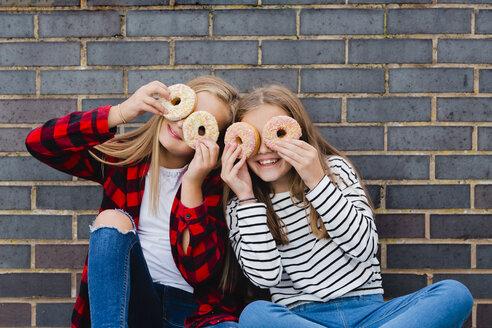 Two girls having fun with doughnuts - NMSF00282
