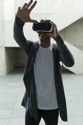 Young man wearing Virtual Reality Glasses raising his hand - JPTF00052