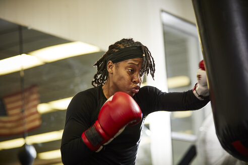 Low angle view of determined female boxer practicing in gym - TGBF00653