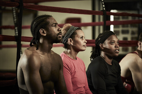 Male and female boxers listening to coach while sitting on boxing ring in gym - TGBF00680