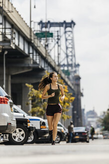 Determined Young Woman Jogging On City Street - TGBF00692
