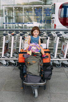 Baby girl sitting on the top of the luggage in a trolley at the airport - GEMF02434