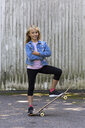 Portrait of smiling blond girl with skateboard - JFEF00906