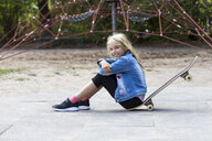 Portrait of smiling blond girl sitting with her skateboard on playground - JFEF00909