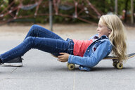 Smiling blond girl with skateboard on playground - JFEF00915