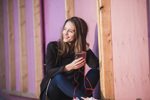 Smiling young woman sitting outdoors listening to music - UUF15646