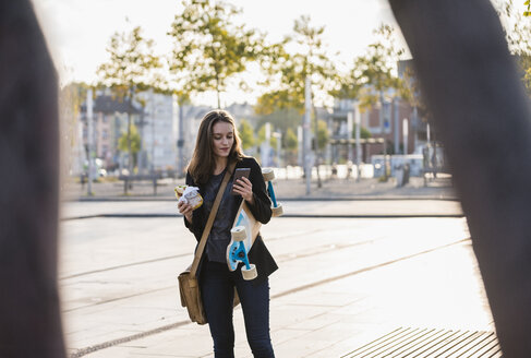Young woman with longboard and snack in the city checking cell phone - UUF15658