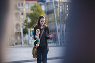 Young woman with longboard and snack in the city checking cell phone - UUF15661