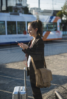 Young woman with luggage at tram station in the city using cell phone - UUF15667
