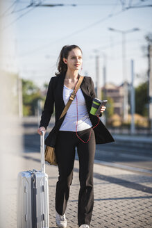 Young woman with luggage in the city on the move - UUF15670
