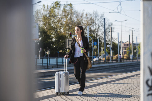 Young woman with luggage at tram station on the move - UUF15673