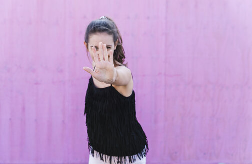 Young woman standing in front of pink wall raising her hand - UUF15685