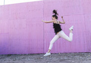 Exuberant young woman jumping in front of pink wall - UUF15688