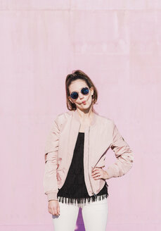 Portrait of young woman wearing sunglasses grimacing in front of pink wall - UUF15694