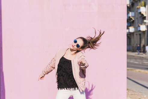 Happy young woman moving in front of pink wall - UUF15700