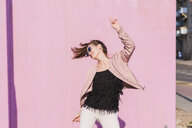 Happy young woman moving in front of pink wall - UUF15703