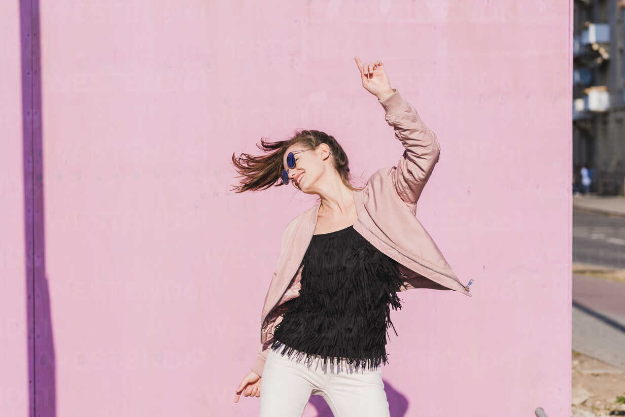 Happy young woman moving in front of pink wall - UUF15703 - Uwe Umstätter/Westend61