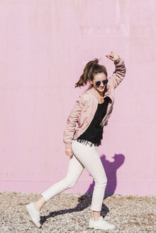 Happy young woman moving in front of pink wall - UUF15706
