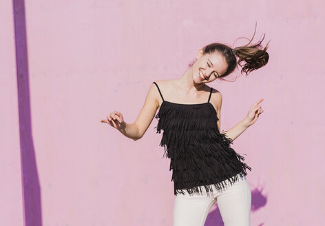 Happy young woman moving in front of pink wall - UUF15709