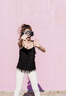 Young woman wearing VR glasses in front of pink wall - UUF15715