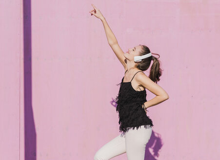 Happy young woman wearing headphones dancing in front of pink wall - UUF15718
