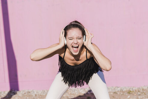 Exuberant young woman wearing headphones screaming in front of pink wall - UUF15721