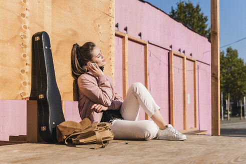 Smiling young woman sitting on platform next to guitar case listening to music - UUF15724