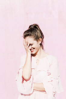 Laughing young woman in front of pink wall - UUF15733