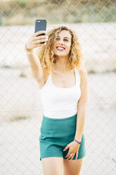 Portrait of blond young woman taking selfie with mobile phone - OCMF00016