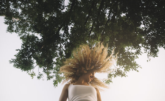 Young woman with blond ringlets tossing her hair - OCMF00019
