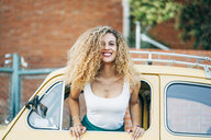 Portrait of happy blond woman leaning out of window of classic car - OCMF00025