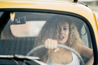 Portrait of surprised blond woman driving classic car - OCMF00028